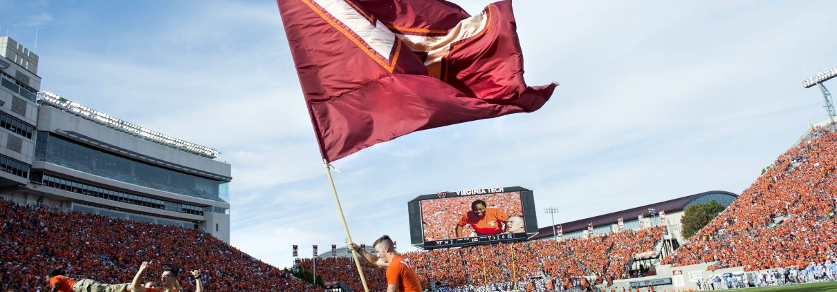 Corp of Cadets member waves VT flag at Lane Stadium, the largest stadium in VA